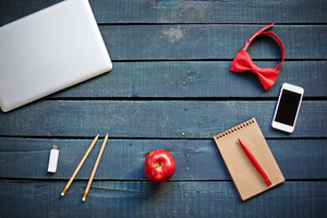 Technological devices, bowtie, red apple, pencils and notebook with pen on workplace