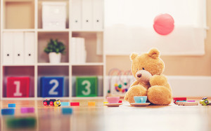 Teddy bear inside a child's play room surrounded by toys