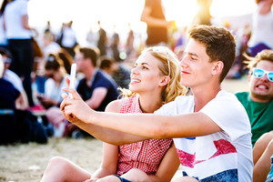 Teenage boy and girl enjoying a summer music festival, sitting on the ground, taking selfie with smart phone