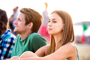 Teenage boy and girl enjoying a summer music festival, sitting on the ground