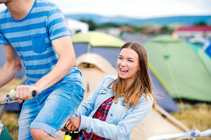 Teenage boy and girl having fun riding bike together at summer music festival in a tent sector