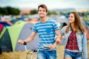 Teenage boy and girl in love with bike at summer music festival in a tent sector