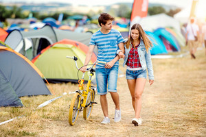Teenage boy and girl in love with yellow bike at summer music festival in a tent sector