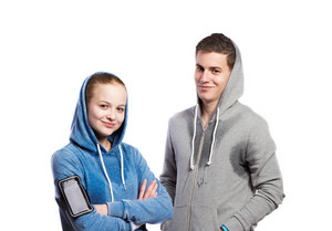 Teenage boy and girl in sweatshirts, wearing phone armband, hoods on heads. Studio shot on white background, isolated.