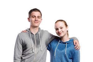 Teenage boy and girl in sweatshirts, with arms around each other. Studio shot on white background, isolated.