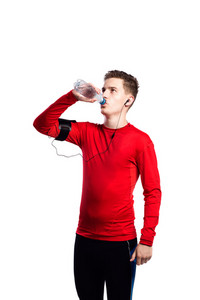 Teenage boy in blue sports sweatshirt, smart phone in his armband, drinking water from bottle.. Handsome young sportsman wearing earphones, listening music. Studio shot on white background, isolated.