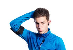 Teenage boy in blue sports sweatshirt, smart phone in his armband. Handsome young sportsman wearing earphones, listening music. Studio shot on white background, isolated.