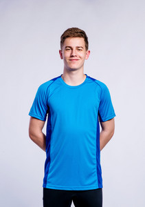 Teenage boy in blue sports t-shirt, young man, studio shot on gray background