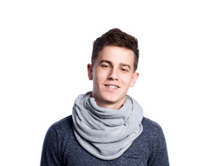 Teenage boy in gray sweater and scarf. Young man smiling. Studio shot on white background, isolated.