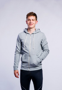Teenage boy in gray sweatshirt, hand in pocket, young man, studio shot on gray background