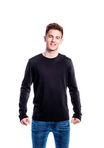 Teenage boy in jeans and black longsleeved t-shirt, young man, studio shot on white background, isolated