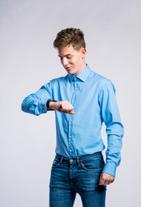 Teenage boy in jeans and blue shirt, young man, studio shot on gray background