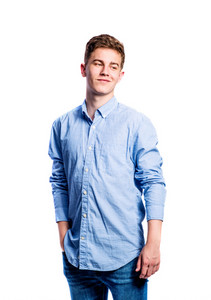 Teenage boy in jeans and blue shirt, young man, studio shot on white background, isolated