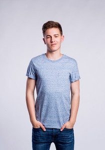 Teenage boy in jeans and blue t-shirt, young man, studio shot on gray background