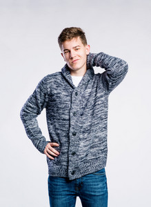 Teenage boy in jeans and dark gray sweater, young man, scratching neck, studio shot on gray background