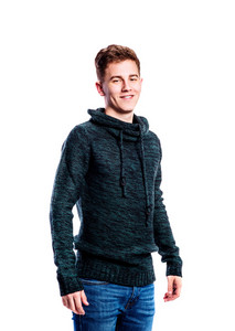 Teenage boy in jeans and dark green sweater, young man, studio shot on white background, isolated