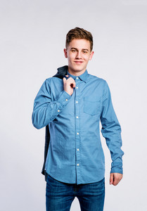 Teenage boy in jeans and denim shirt, young man, studio shot on gray background