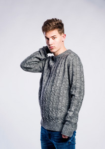 Teenage boy in jeans and gray sweater, young man, studio shot on gray background