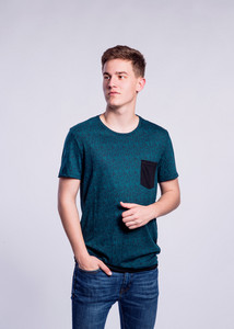 Teenage boy in jeans and green t-shirt, young man, studio shot on gray background