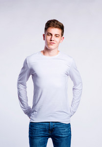 Teenage boy in jeans and white long sleeved t-shirt, young man, studio shot on gray background