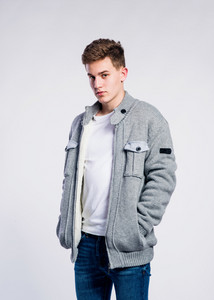 Teenage boy in jeans,  white t-shirt and jacket, young man, studio shot on gray background