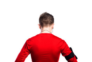 Teenage boy in red sports sweatshirt with earphones, listening music. Handsome young sportsman wearing phone armband. Studio shot on white background, isolated. Rear view.