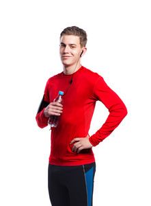 Teenage boy in red sports sweatshirt with earphones, listening music, holding water bottle. Handsome young sportsman wearing phone armband. Studio shot on white background, isolated.
