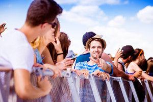 Teenage boy with his friends at summer music festival standing under the stage at the crowd control barrier