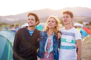 Teenage boys and girl at summer music festival enjoying themselves, sunset