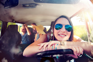 Teenage boys and girls inside an old campervan on a roadtrip, girl driving, sunny summer day