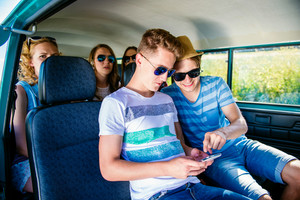 Teenage boys and girls inside an old campervan, playing with smart phone, roadtrip, sunny summer day