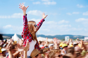 Teenage couple at summer music festival under the stage in a crowd enjoying themselves. Handsome man giving beautiful young woman piggyback, arms in the air.