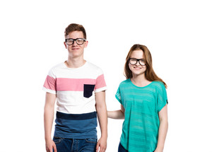 Teenage couple wearing eyeglasses, smiling. Young woman in green t-shirt holdidng man in striped t-shirt. Studio shot on white background, isolated.