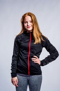 Teenage girl in black sweatshirt and fitness leggings, arm on hip, young woman, studio shot on gray background