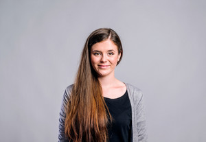 Teenage girl in black t-shirt and gray cardigan, smiling, young beautiful woman, studio shot on gray background