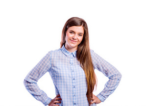 Teenage girl in blue checked shirt, arms on hips, young beautiful woman, studio shot on white background, isolated
