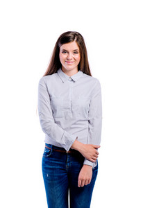 Teenage girl in blue dotted shirt and jeans, young beautiful woman, studio shot on white background, isolated