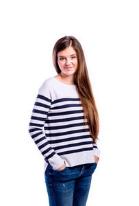 Teenage girl in blue striped sweater and jeans, hands in pockets. Young beautiful woman, studio shot on white background, isolated