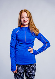 Teenage girl in blue sweatshirt and fitness leggings, arm on hip, young woman, studio shot on gray background