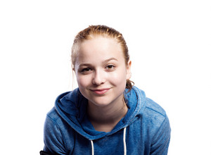 Teenage girl in blue sweatshirt, smiling. Beautiful young sportswoman, studio shot on white background, isolated.