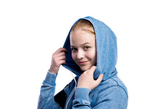Teenage girl in blue sweatshirt, wearing phone armband, holding hood. Beautiful young sportswoman, studio shot on white background, isolated.