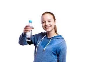 Teenage girl in blue sweatshirt, wearing phone armband, holding water bottle, smiling. Beautiful young sportswoman, studio shot on white background, isolated.