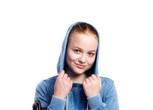 Teenage girl in blue sweatshirt, wearing phone armband, hood on head. Beautiful young sportswoman, studio shot on white background, isolated.