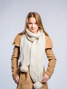 Teenage girl in brown coat and knitted scarf, young woman, studio shot on gray background