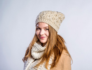 Teenage girl in brown coat and woolen scarf and hat, young woman, studio shot on gray background