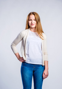 Teenage girl in jeans and beige cardigan, young woman, studio shot on gray background