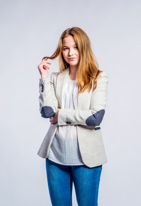 Teenage girl in jeans and beige jacket, young woman holding hair, studio shot on gray background