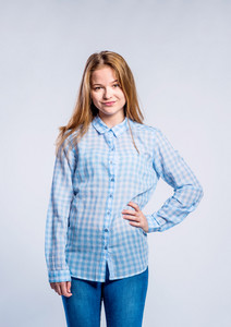 Teenage girl in jeans and blue checked shirt, young woman, hand on hip, studio shot on gray background