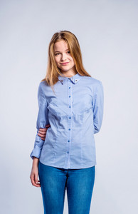 Teenage girl in jeans and blue checked shirt, young woman, studio shot on gray background