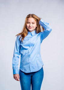 Teenage girl in jeans and blue shirt, young woman holding hair, studio shot on gray background